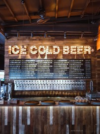 """a wall behind the bar with a long list of beers and a huge sign """"Ice Cold Beer"""""""