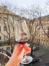 Red wine in a glass with residential buildings in the background. Sunny, early spring afternoon which was perfect for spending time on the small balcony.