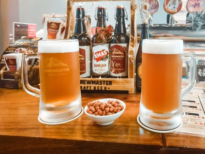 Two pints of beer with a small plate of peanuts.