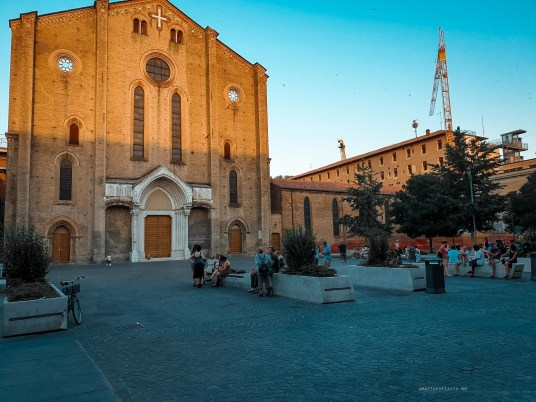 A typical afternoon in Bologna with all benches outside a church occupied by people of all ages eating, drinking and chatting.