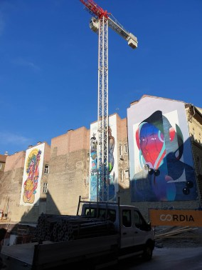 Construction side with three large scale murals in the background. They're modern-style, colourful depictions of people.