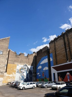 Parking with brick buildings in the background painted with large murals. One of them shows a blue sky with white clouds, the other one pictures a young girl curled up in an outline of a house.