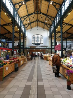 Small market hall with tall ceilings (painted yellow in this case). There are two rows of tables filled with fruits and vegetables and an elderly man standing in front of one of the tables.