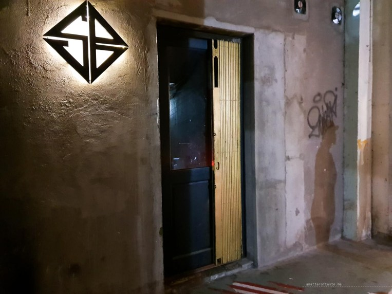 Plain concrete wall with Snuffbox's logo and nondescript door - entrance to the speakeasy bar.