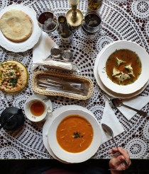 a top view of a table at a Jewish restaurant in Lublin. There is a tomato soup, a chicken soup with dumplings and a plate of hummus with bread.