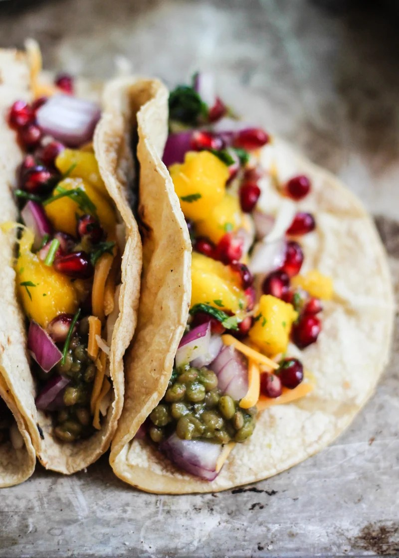 Vegetarian lentil tacos in an amazing homemade salsa verde green sauce then topped with a mango-pomegranate pico. Healthy & so flavorful!
