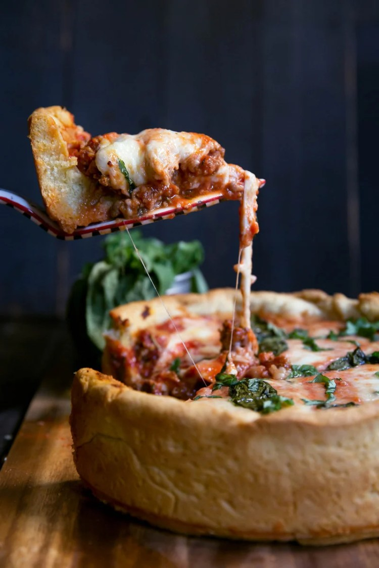serving slice of homemade deep dish pizza