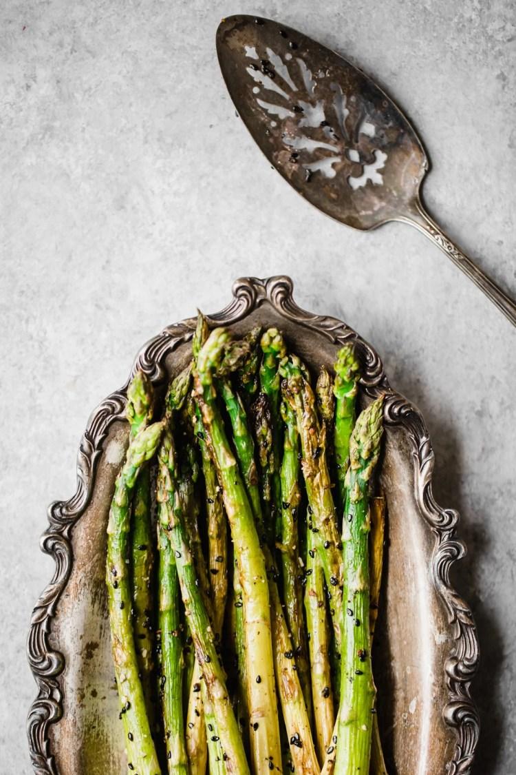 sesame garlic roasted asparagus on a silver platter