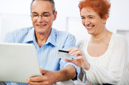 Happy couple using credit card to donate online.