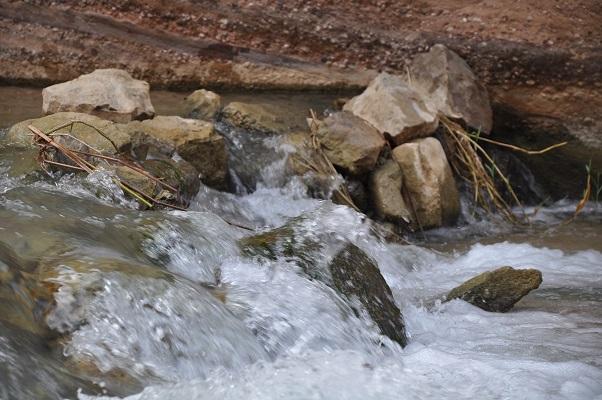 Stromend rivierwater tijdens kloofwandeling Wadi El Hasa tijdens een wandelreis van SNP door Jordanië