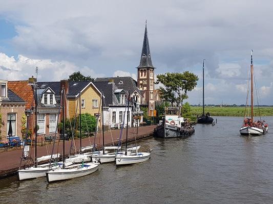 Haven en kerk Woudsend tijdens een wandeling over het ELfstedenpad van IJlst naar Balk