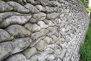 Wandelen over het Grebbeliniepad bij zandzakken bij het Valleikanaal