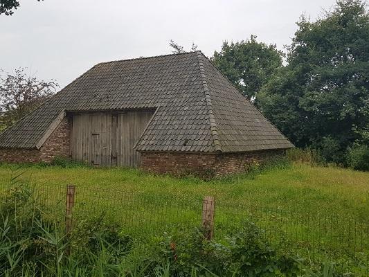 Wandelen over het Peelpad bij schuur bij kasteel in Heusden