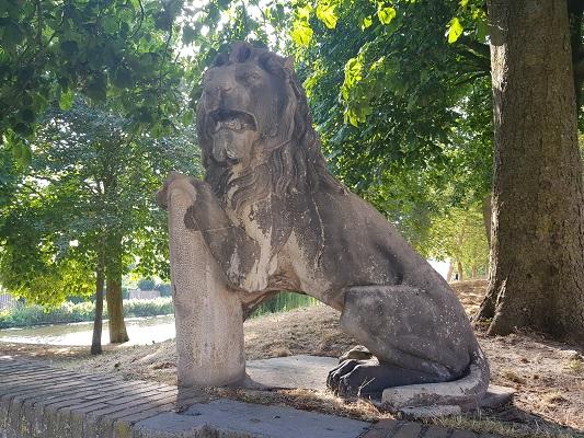 Wandelen over het Westerborkpad van 't Harde naar Elburg bij leeuw bij toegang tot Elburg