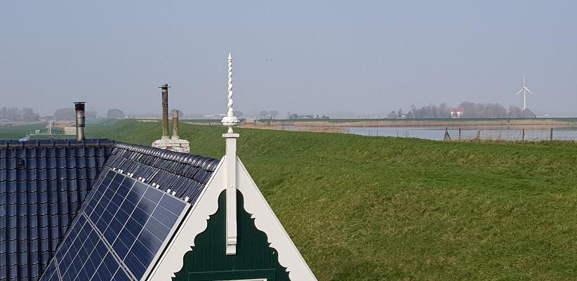 Wandelen over het Noord-Hollandpad van Nieuwesluis naar Den Oever bij een versiering op het dak van een boerderij