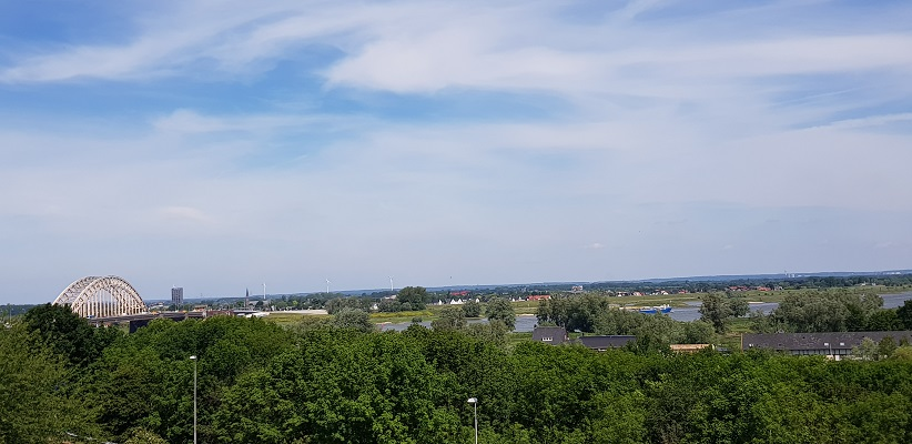 Wandelen buiten de binnenstad van Nijmegen over het Berg en Dalpad met zicht op de Waal en de Waalbrug