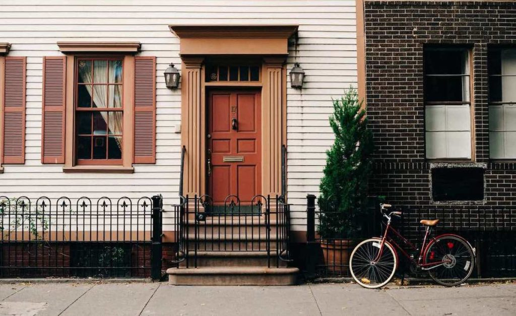Image of a townhouse with a red door. Bike in front of house.