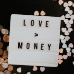 Letter board saying love is greater than money with candy hearts and coins in the back