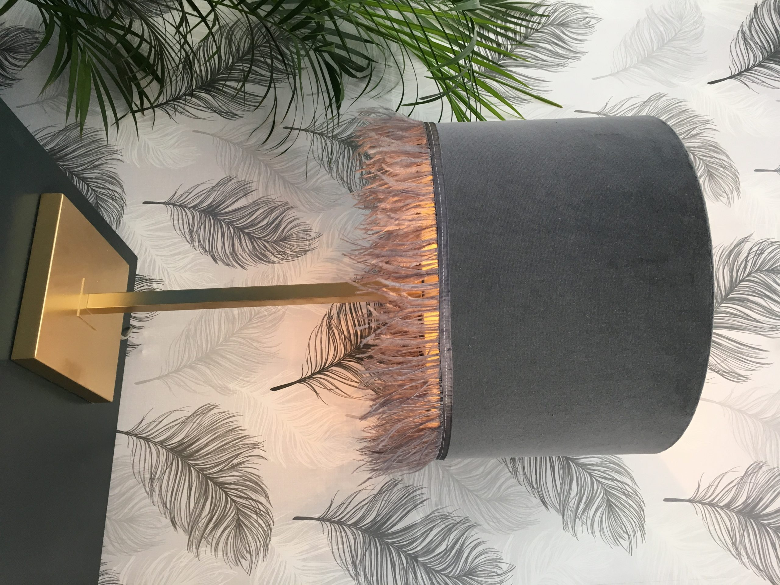 Gold lamp base with grey velvet lampshade with grey ostrich feather fringing
