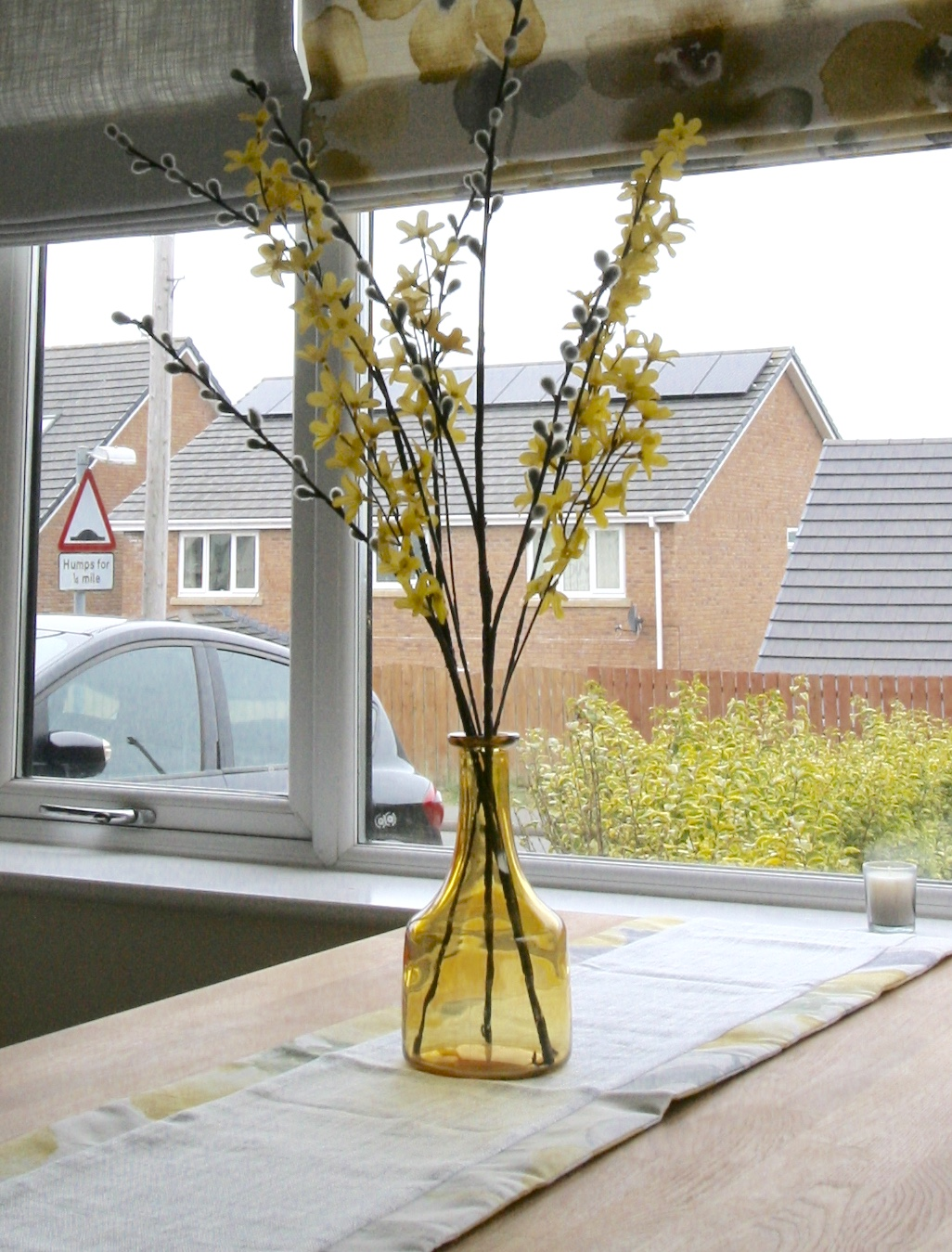 Yellow glass vase from Oxfam with artificial flower