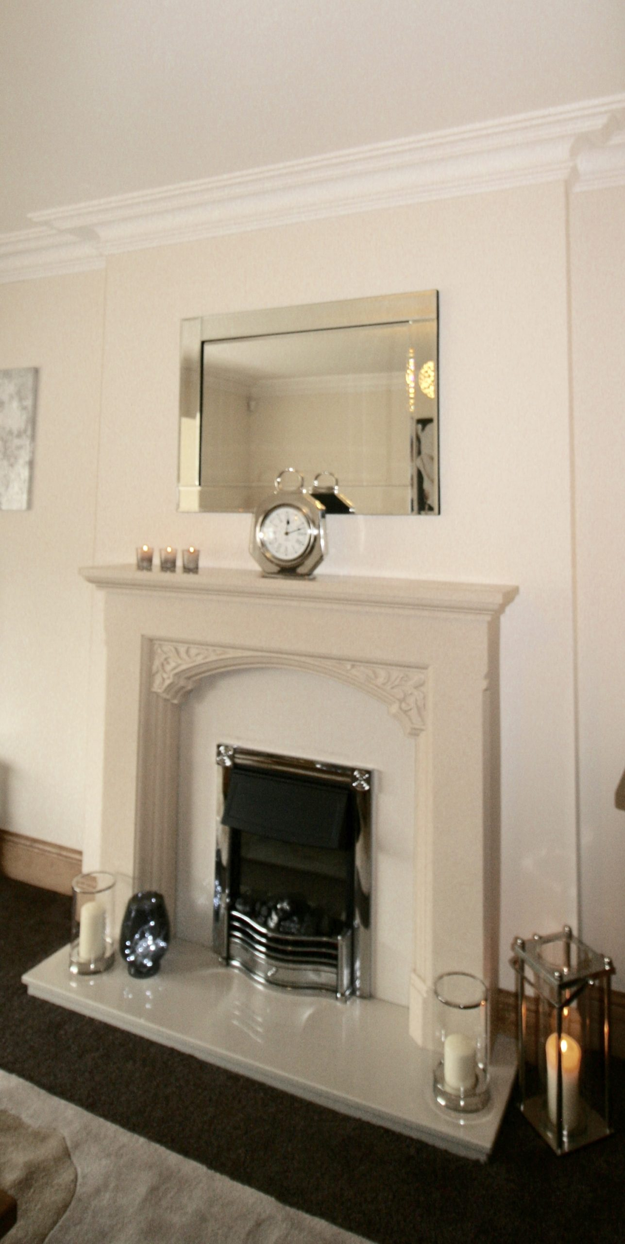 Simple hurricane lanterns on the hearth and smoked grey glass tealights on the mantelpiece, all from Dunelm