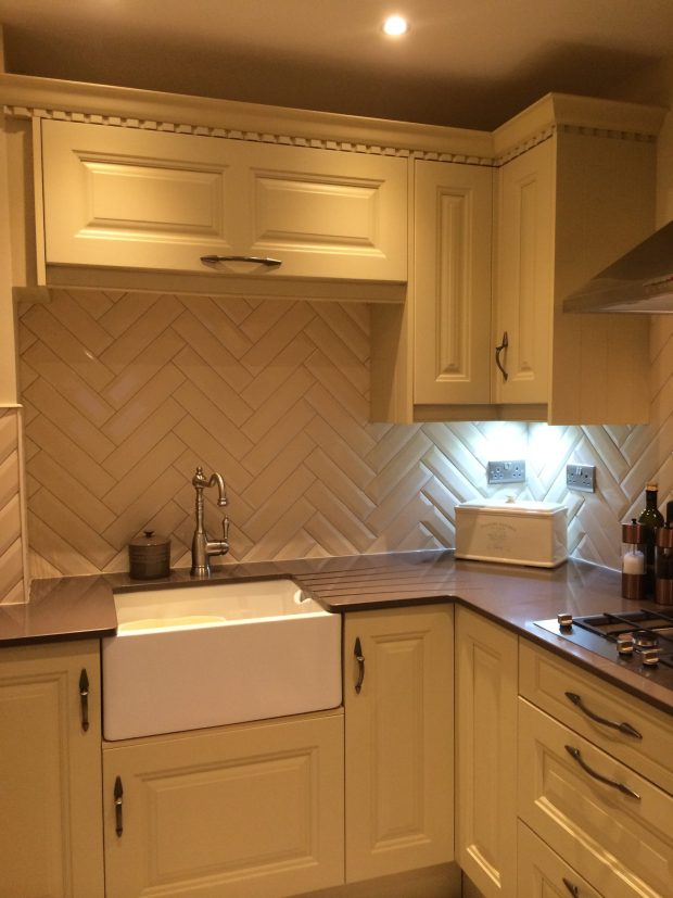 Cream shaker style kitchen with Belfast sink and herringbone effect metro tiles