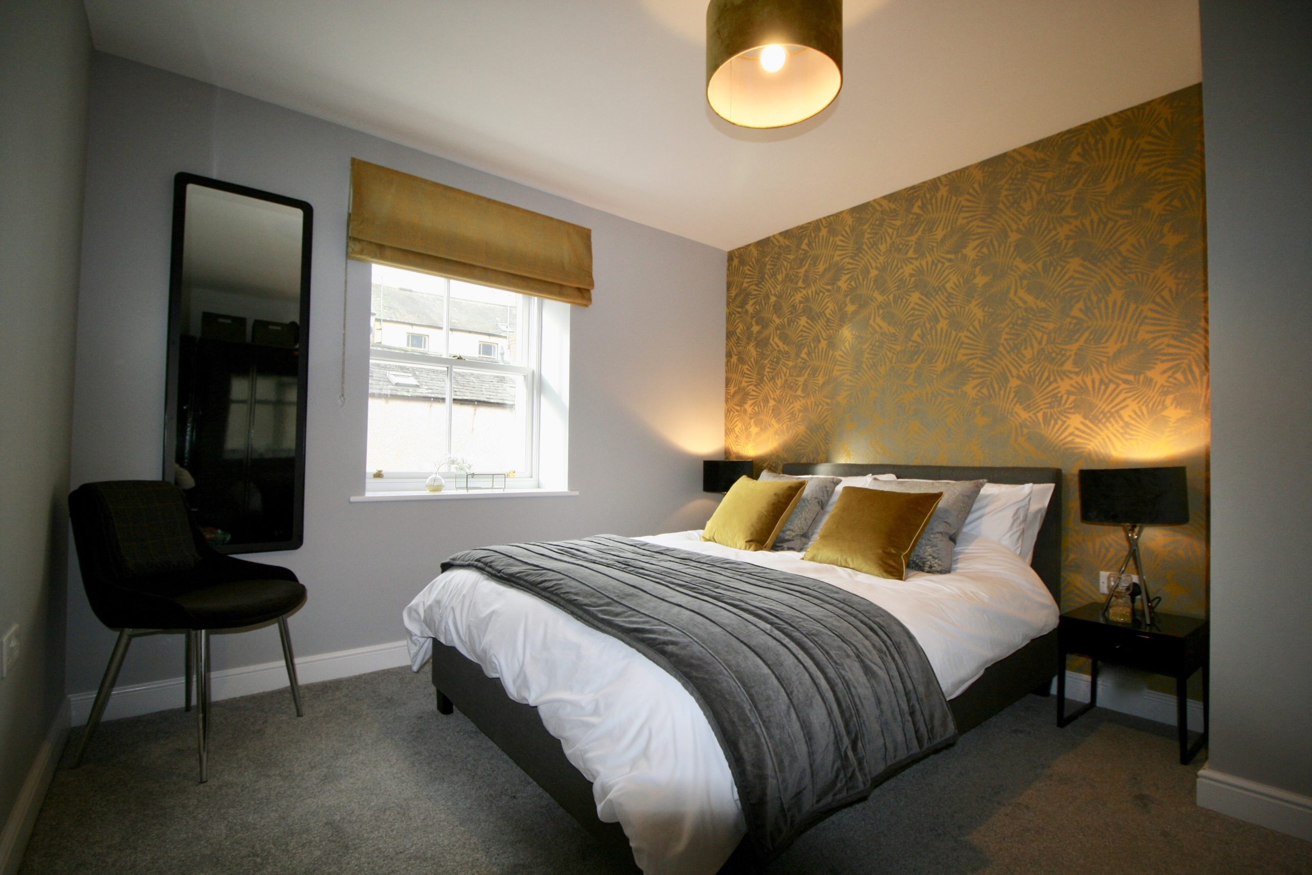 Master bedroom decorated in charcoal grey, mustard and black in show home designed by Amelia Wilson