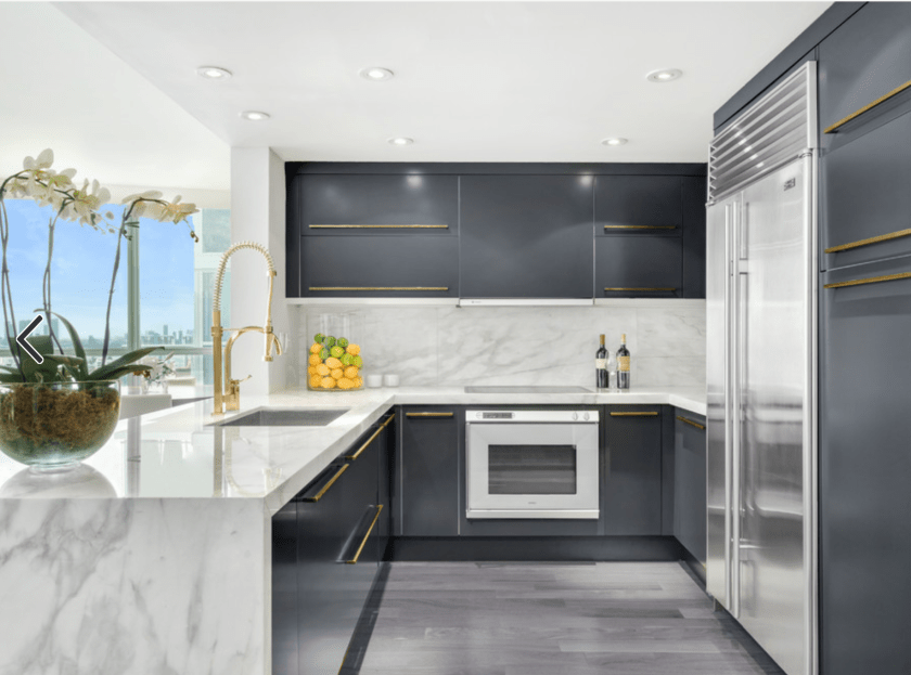 Contemporary grey gloss kitchen with marble worktop and gold taps and gold handles