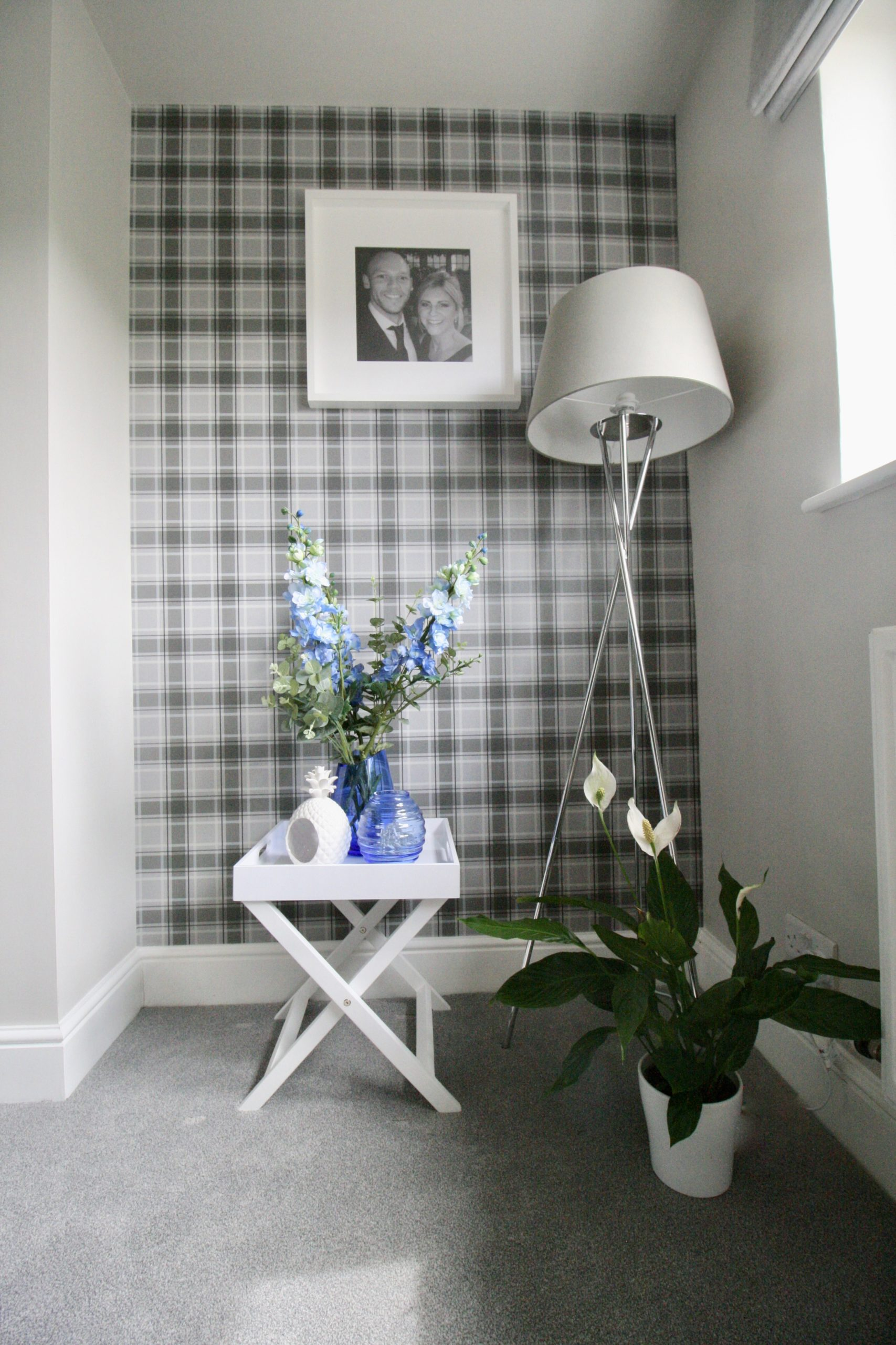 Chrome tripod floor lamp with grey shade grey plaid wallpaper in TV room