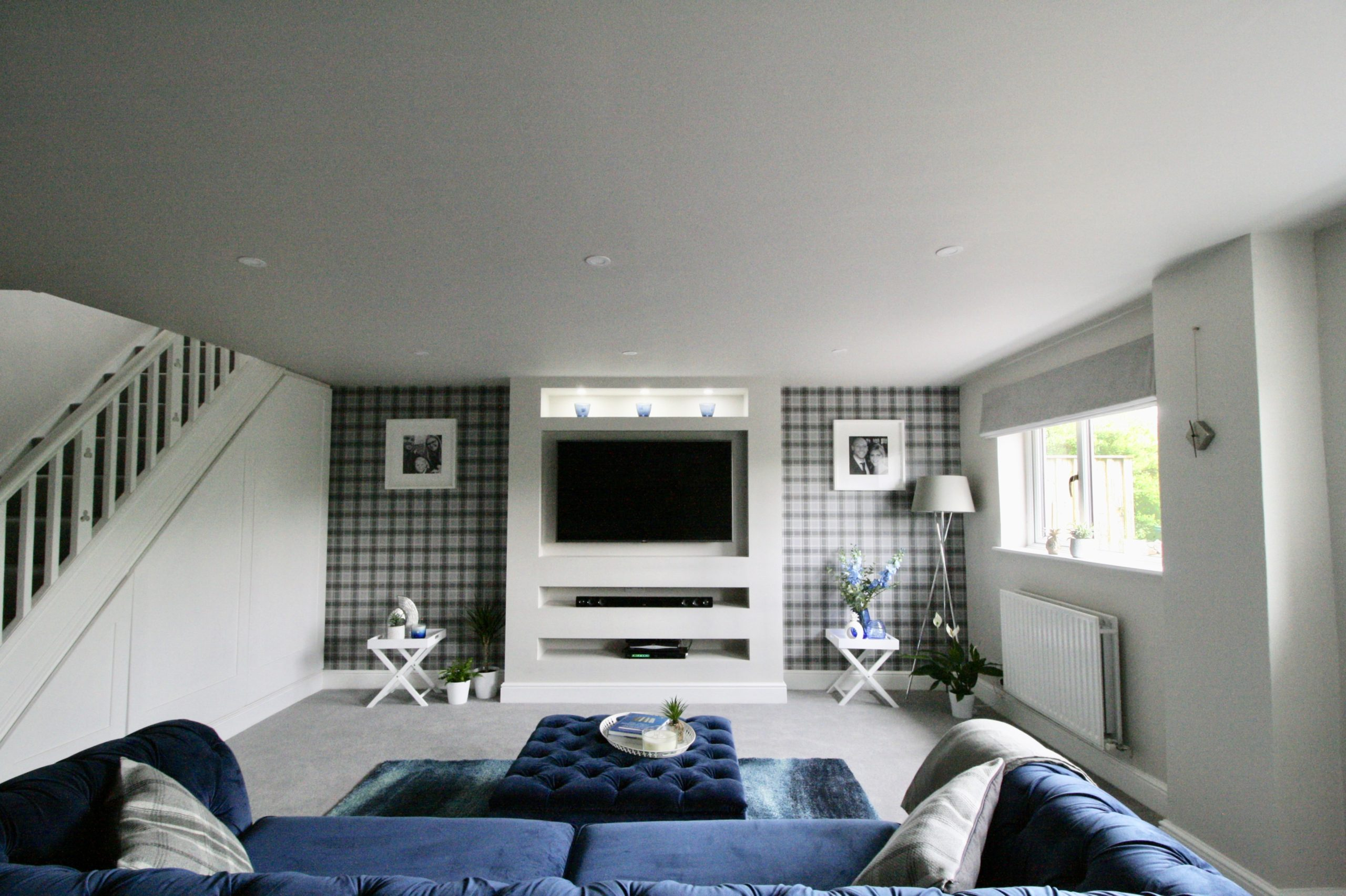 Media wall in grey TV room with wall mounted concealed TV and concealed lighting