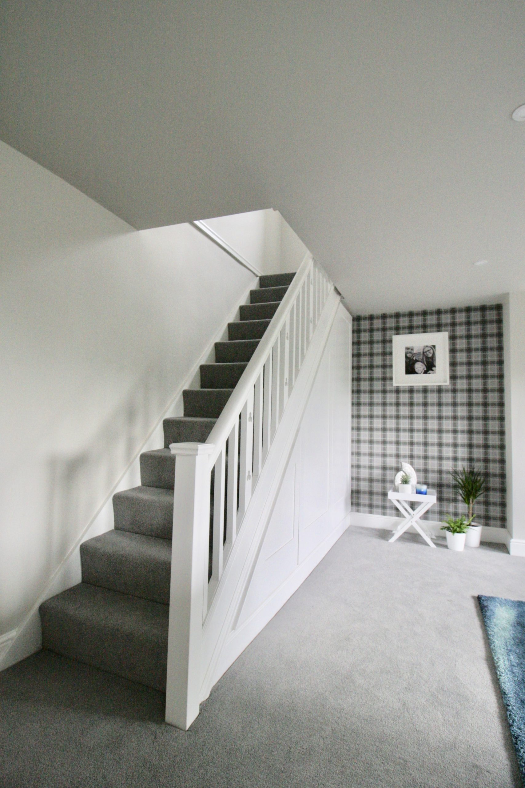 White painted staircase with square newel post in grey and white TV room with grey carpet