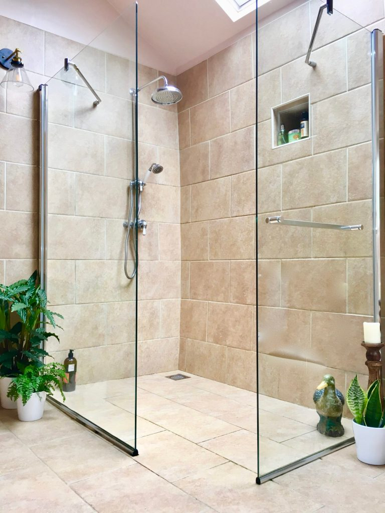 Large walk in wet room in bathroom with large roof light and floor to ceiling tiles