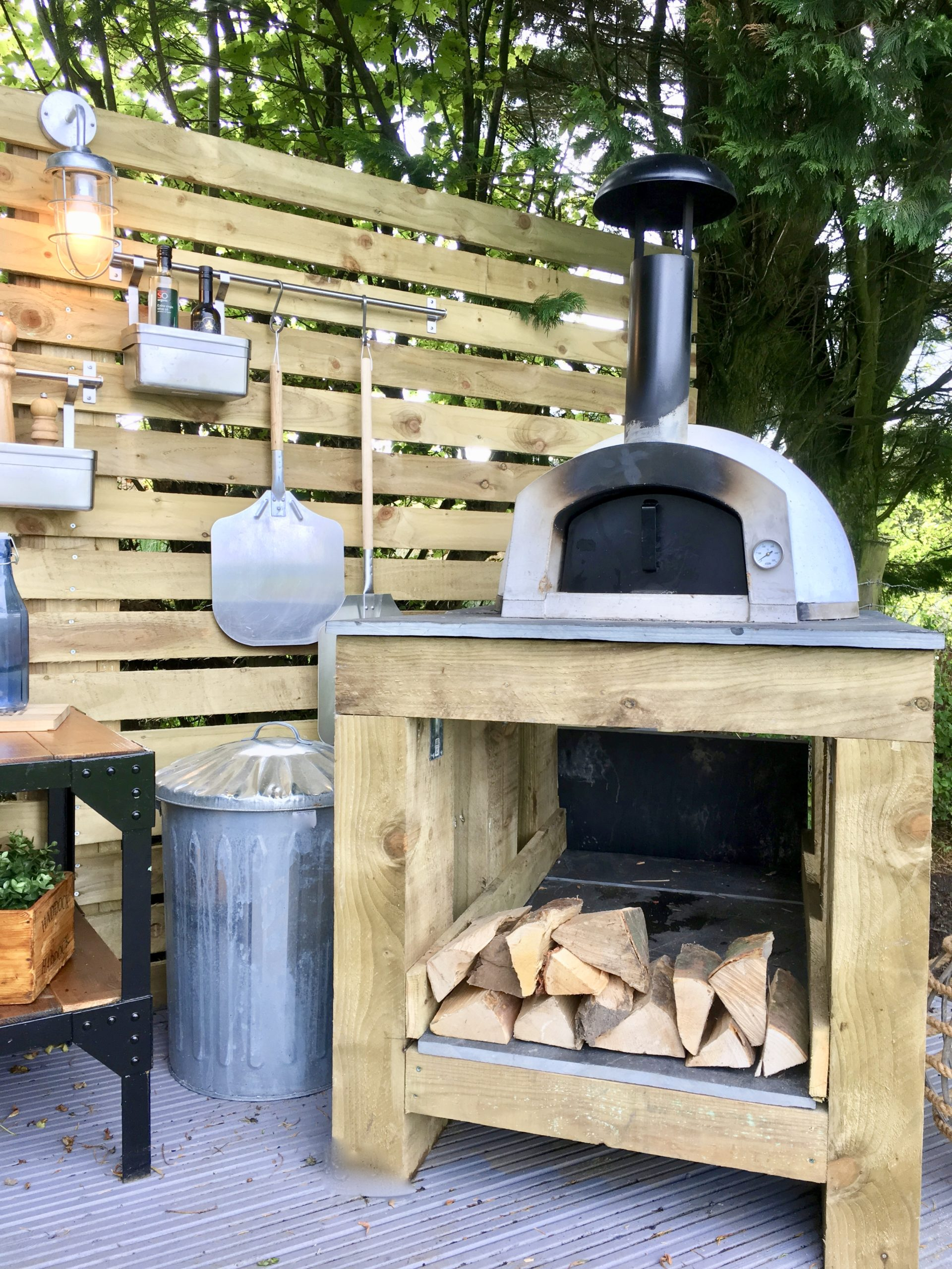 Pizza oven in outdoor kitchen on stand made from rustic sleepers