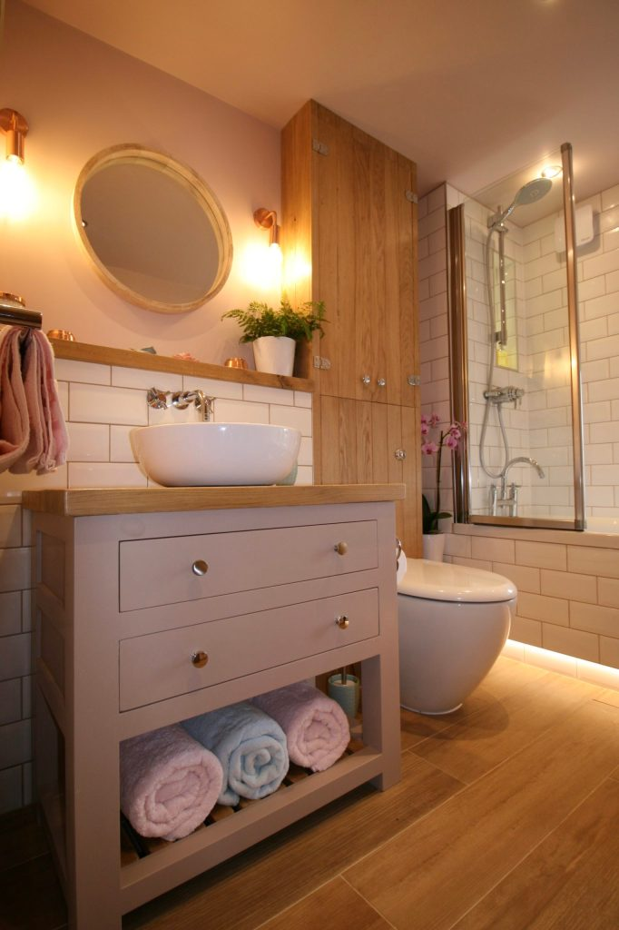 Over bath shower with hinged screen in bathroom designed by Amelia Wilson