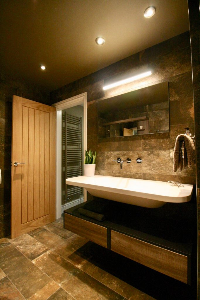 Wet room with Bruno Des Alpes wall and floor tiles and floating basin