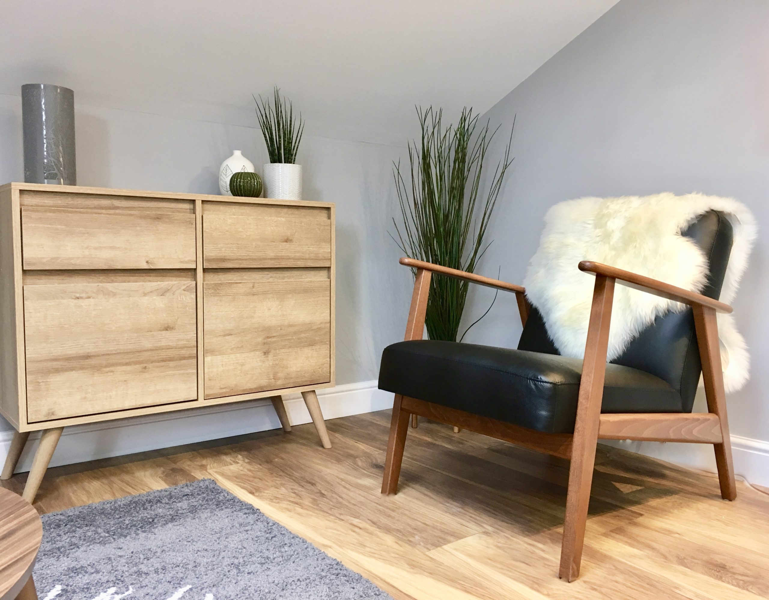 Danish style armchair with sheepskin rug and skandi style oak effect sideboard in show home designed by Amelia Wilson Interiors Ltd