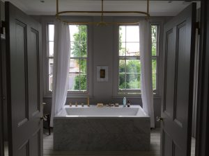 White, grey and marble bathroom in Victorian property with gold fixtures