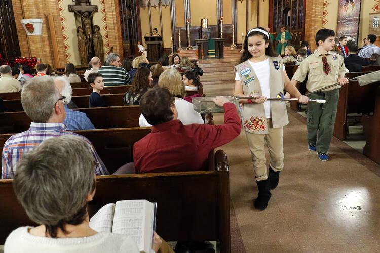 Girl Scout Julia Ocasio, 13 y Boy Scout Thomas Perotta, 10, utilizan cestas de recogida durante una misa dominical scout, el 7 de febrero en el Inmaculado Corazón de María Iglesia en el barrio de Windsor Terrace del barrio neoyorquino de Brooklyn.  (SNC foto / Gregory A. Shemitz)
