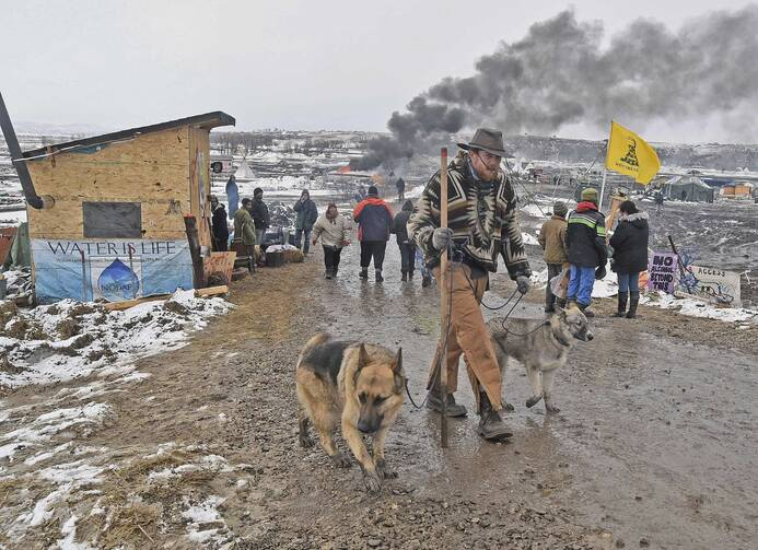 """Jasper Spillman, de Lawrence, Kan., Se suma a otras que salen de los """"protectores de agua"""" campo principal el 22 de febrero de 2017, cerca de bola de cañón, Dakota del Norte (Tom Stromme / El Bismarck Tribune vía AP)"""
