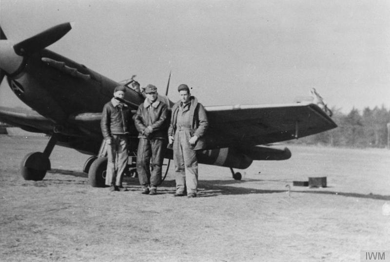 Airmen of the 336th Fighter Squadron, 4th Fighter Group with a clipped wing Spitfire Mk. Vb (MD-A), 1943. Handwritten caption on reverse: '19A. KP. Fall, 1942. Great Sampford Satellite Field. 336th crew by 336th Spit Mk. Vb. Wings clipped by sawing off wing & pounding in board then carving and painting it. MD-A, red/blue wheel. Source -Bill Chick, Megura.'