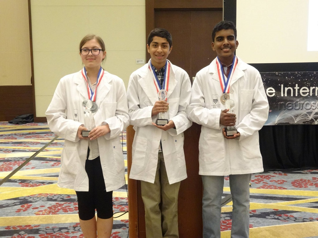 Indian American whiz kid Sojas Wagle (center) is the 2017 World Brain Bee Champion. At left is Milena Malcharek of Poland, in second place, and at right is Elwin Vethamuthu of Malaysia who finished third in the neuroscience competition for teenagers.