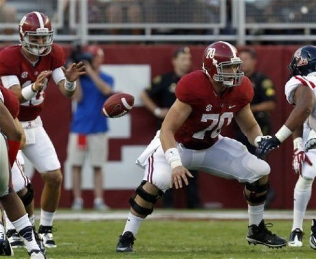 Alabama offensive linesman Ryan Kelly (70) blocks out after snapping the ball to quarterback A.J. McCarron (10) during the first half of an NCAA college football game against Mississippi on Saturday, Sept. 28, 2013, in Tuscaloosa, Ala. (AP Photo/Butch Dill)