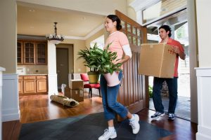 a man and a girl moving plants and carton inside the house | American Home Services | Door Orlando