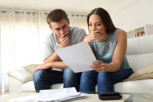 a couple thinking and holding a paper | American Home Services | Insurance Orlando