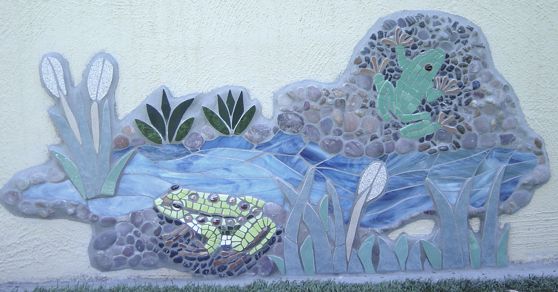 Image of a glass, peeble and ceramic mosaic featuring two frogs, a pond and water grasses
