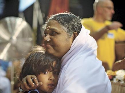 """""""אמה"""" מחבקת צעירה באירוע צדקה בניו יורק. בארה""""ב לבדה, יש לה שמונה אשרמים. צילום: ניו יורק טיימס"""