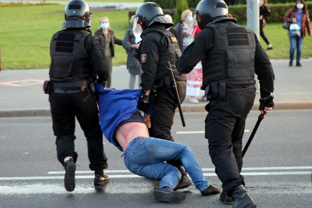 Riot police officers detain a man during an opposition rally to protest