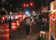 "Ben Kleppinger/ben.kleppinger@amnews.com A runner with the ""Knob Greek"" team makes her way down Main Street in Danville."