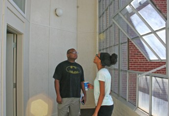 Kendra Peek/kendra.peek@amnews.com Deitrick Perrin and his daughter Anajah Perrin look at the three-seasons room in one of the apartments in the Goodall Apartments building, officially opened on Friday.