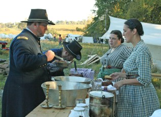 Kendra Peek/kendra.peek@amnews.com Kimberlee Berezuk, center, and Sherrie Williams, right, act as contracted cooks during the Perryville reenactment, serving the men in the unit, including Berezuk's husband, Pete, left.